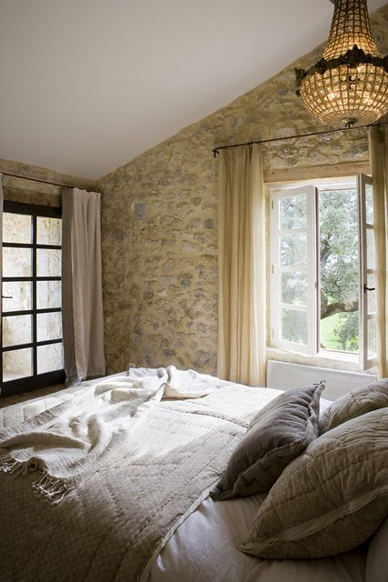 Weathered stone wall, antique crystal chandelier, and #Frenchfarmhouse charm in a small bedroom on Hello Lovely Studio