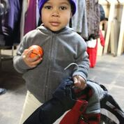 A mixed child with a grey hooded sweater, a new coat and a toy basketball