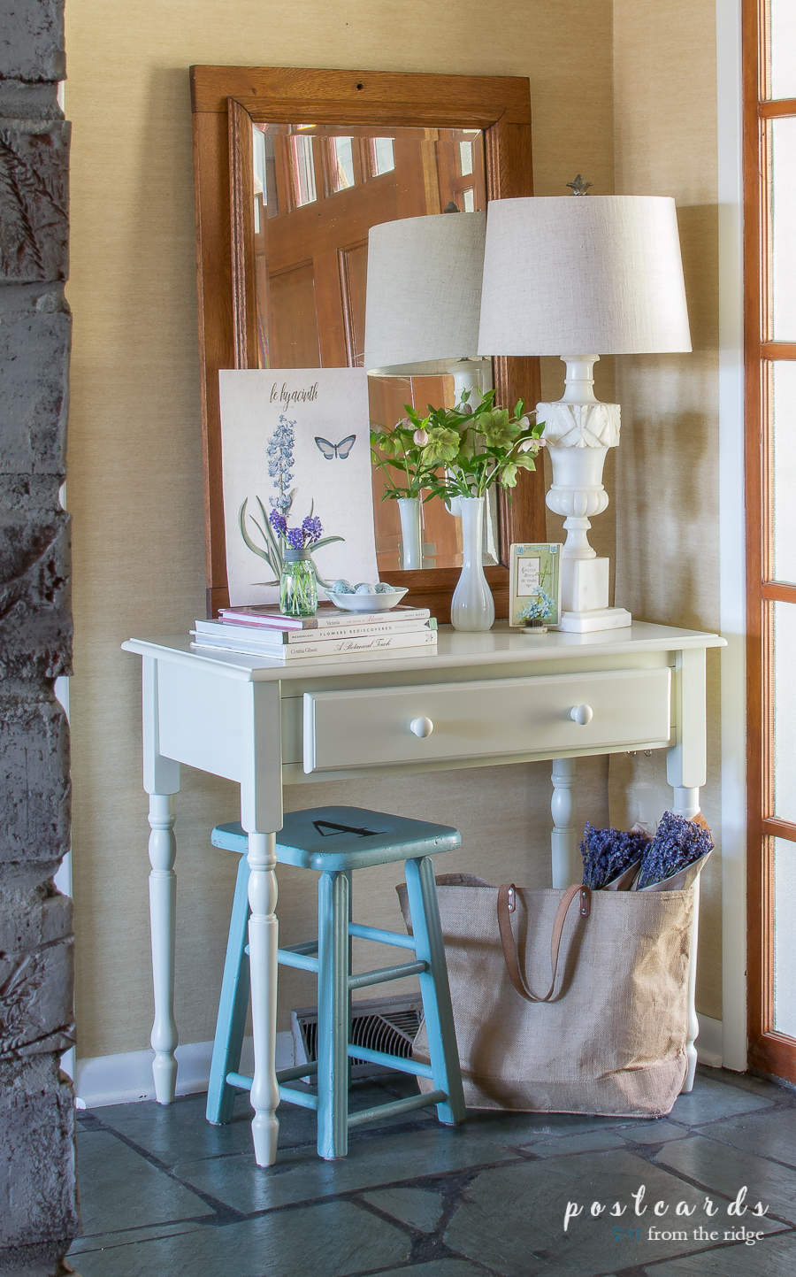 white desk and blue stool in an entry with vintage flagstone floor