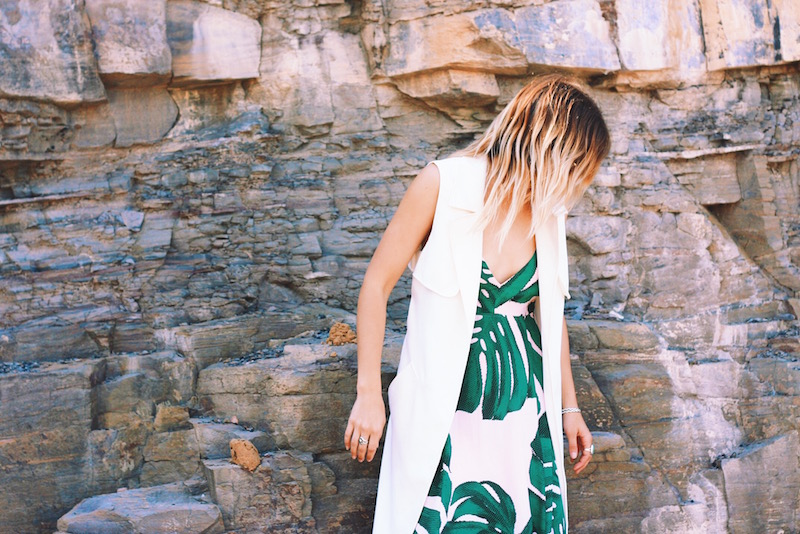 A banana tropical leaf printed dress from Express Festival style worn by Bryn Newman shot on the beaches in northern wollongong, a city outside of Sydney, Australia with beautiful white sand beaches and rock pools