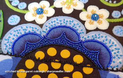 Peacock and royal blue beads are used to fill an element of the large blue flower (Japanese bead embroidery)