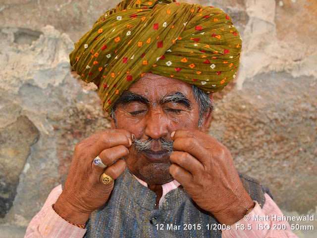 Rajasthani turban; pagari; moustache; both hands; Matt Hahnewald Photography; Facing the World; photography; photo; image; outstanding; fantastic; favourite; superior; excellent; inspirational; vibrant; breathtaking; Nikon D3100; Nikkor AF-S 50mm f/1.8G; prime lens; 50mm; 4 : 3 aspect ratio; horizontal format; closeup; portrait; portraiture; headshot; en face; front view; outdoor; colour; colourful; world cultures; cultural; character; personality; real people; human; human head; human face; human eyes; facial expression; eye contact; Rajasthani pagari; turban; consent; empathy; rapport; encounter; relationship; emotion; mood; environmental portrait; ethnic portrait; travel; travel portrait; travel destination; tradition; Jaisalmer; Rajasthan; India; one person; male; adult; Indian man; posing; authentic; incredible; awesome; preparing; twirling his beard; body language; gesture; Rajasthani man; street portrait