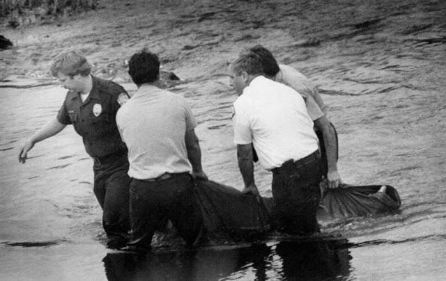 Imagem da polícia retirando um corpo do rio