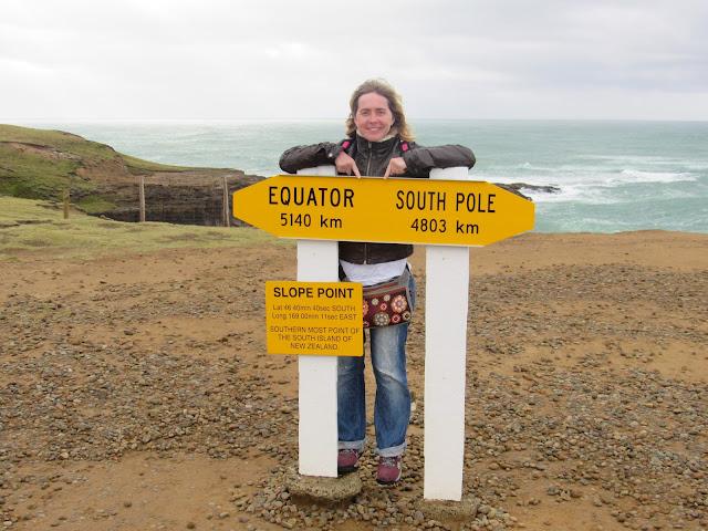Tatiana detrás del cartel de Slope Point que indica la distancia al ecuador y al polo sur