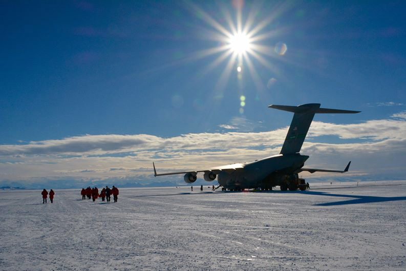 A giant plane sits on ice as a group of people walk up to it