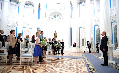 At a ceremony in the Kremlin, Vladimir Putin and young citizens of Russia.