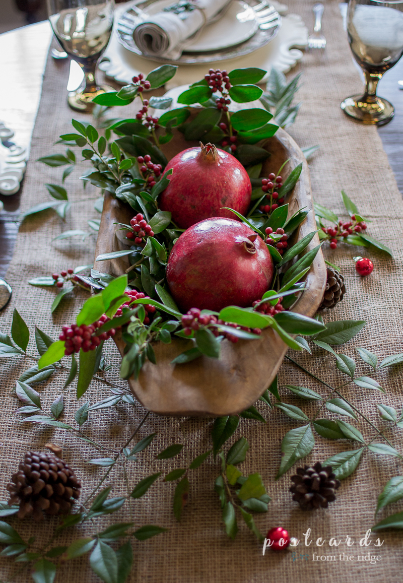 Beautiful Christmas centerpiece using pomegranates, holly, and other natural items in a wooden dough bowl.