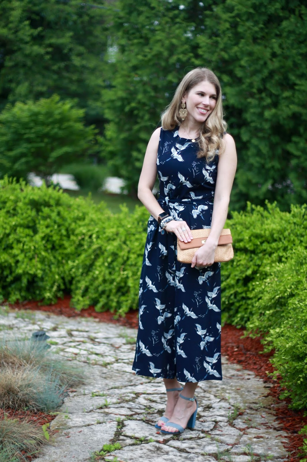 navy blue crane print jumpsuit, denim heels, straw clutch