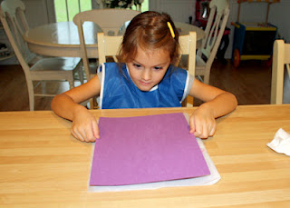 She lightly pressed a piece of construction paper onto the painted surface per the instructions.