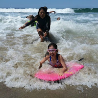 Keiki Camp Director Ashley Dizon teaches camper Malia how to boogie board in the ocean in Malibu