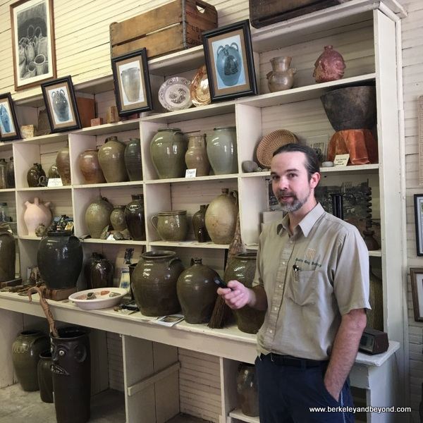 Master Potter Justin Guy in front of historic pottery collection in Old Edgefield Pottery in Edgefield, South Carolina