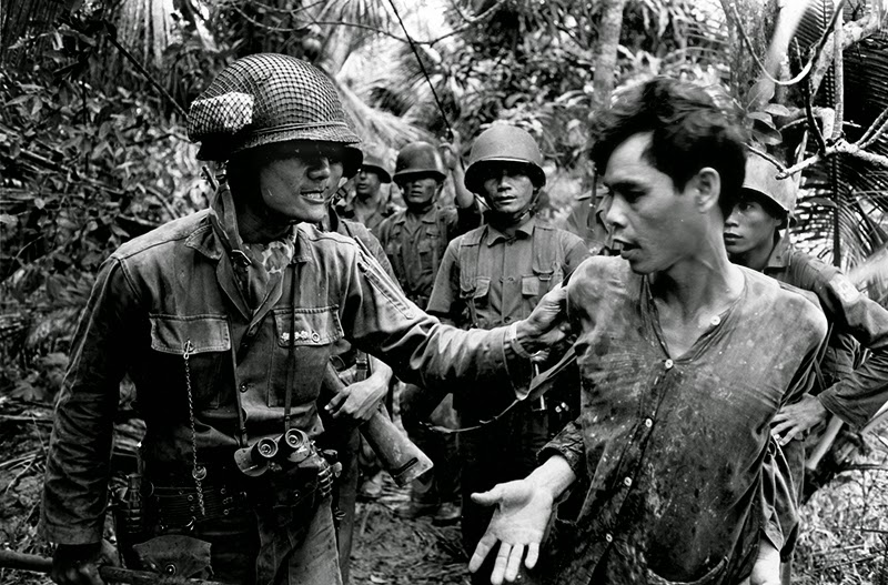 A vietnamese battalion commander captain thach quyen left interrogates a captured viet cong suspect on tan dinh island mekong delta in 1965
