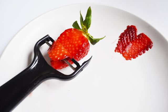 un pelador negro de patatas, dos laminas finas de fresa, y una fresa que estoy cortando con el pelador