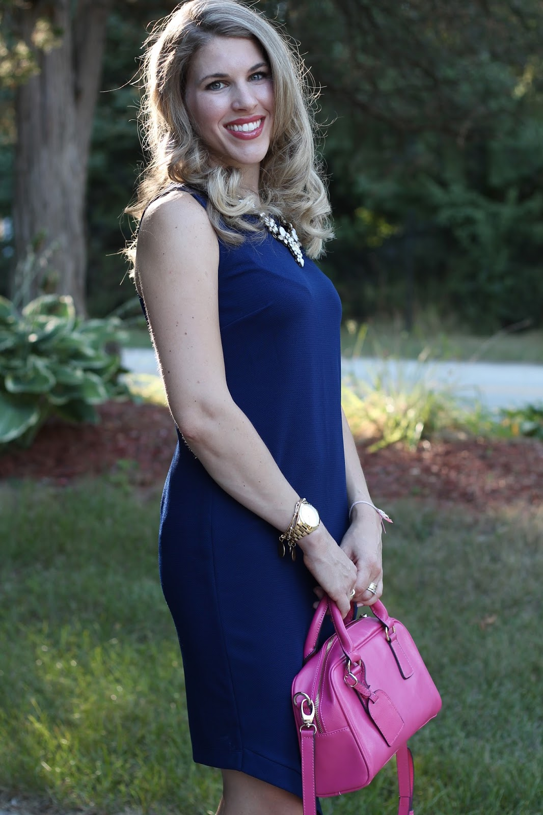sleeveless navy envelope dress, pink heels, pink bag, white statement necklace,