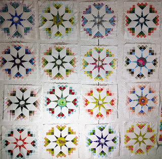 Eight-pointed star variations have medium and pastel colors surrounding white fabric stars. The center circles haven't been chosen yet.