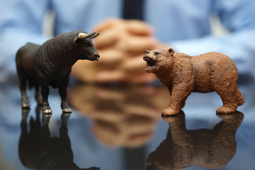 miniature bull and bear with man on the background
