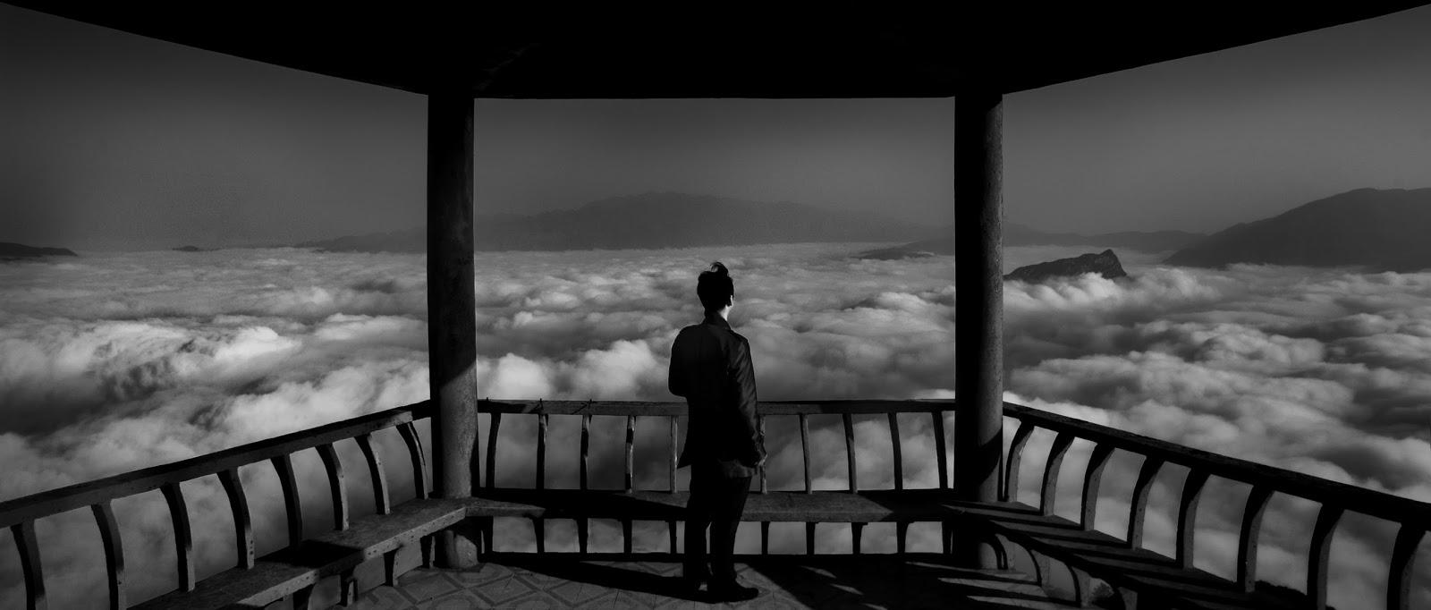 Homem do alto de uma torre a contemplar, por cima, a paisagem de montanhas cobertas por nuvens: ilustra a seção a respeito dos textos das linhas de ''Kuan / Contemplação (a Vista)'', um dos 64 hexagramas do I Ching, o Livro das Mutações