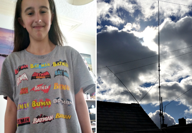 My teenage daughter in a batman t-shirt and the radio antennas against a cloudy sky.