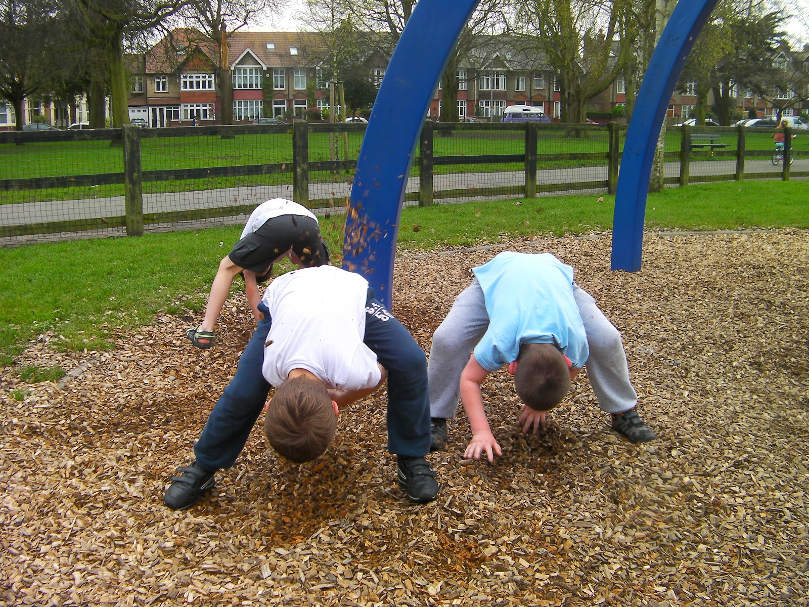 boys piling up woodchips in milton park play area