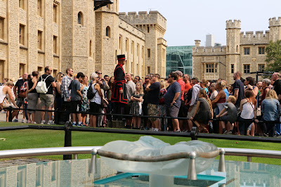 Yeoman Warder giving a tour of the Tower   with the scaffold site in the foreground
