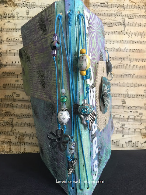 Spine of the journal with lots of beads in blues, greens hanging from cobalt hemp with flower & butterfly charms.
