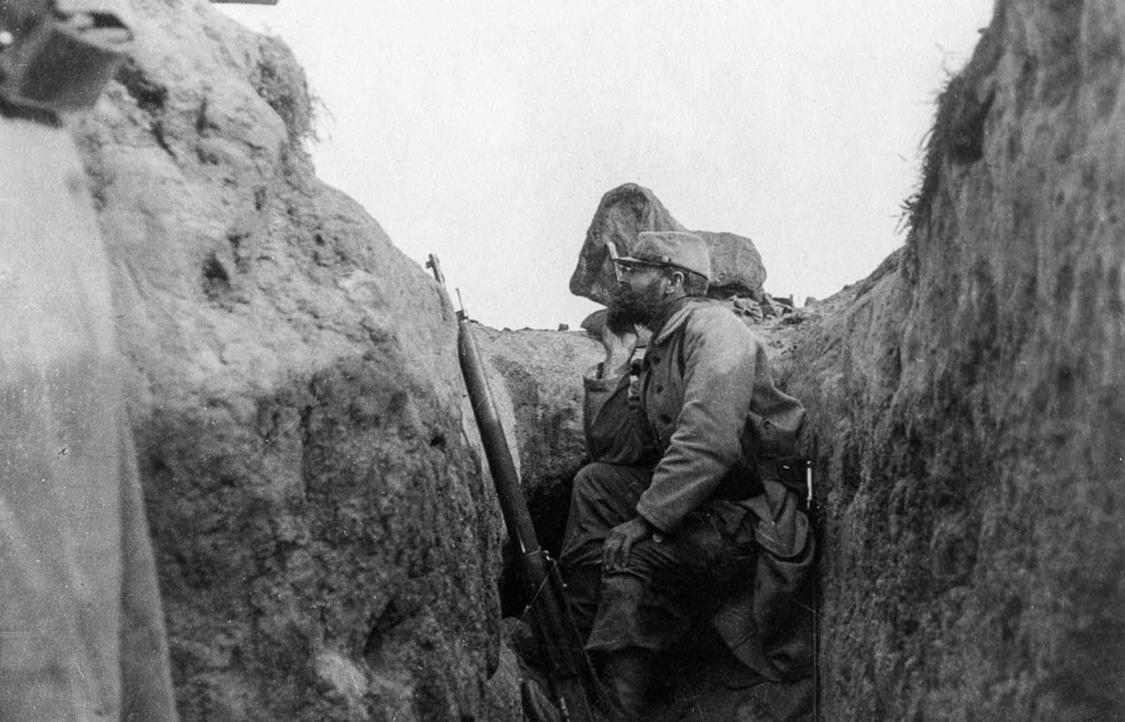 Un soldado francés mira por encima del borde de una zanja.