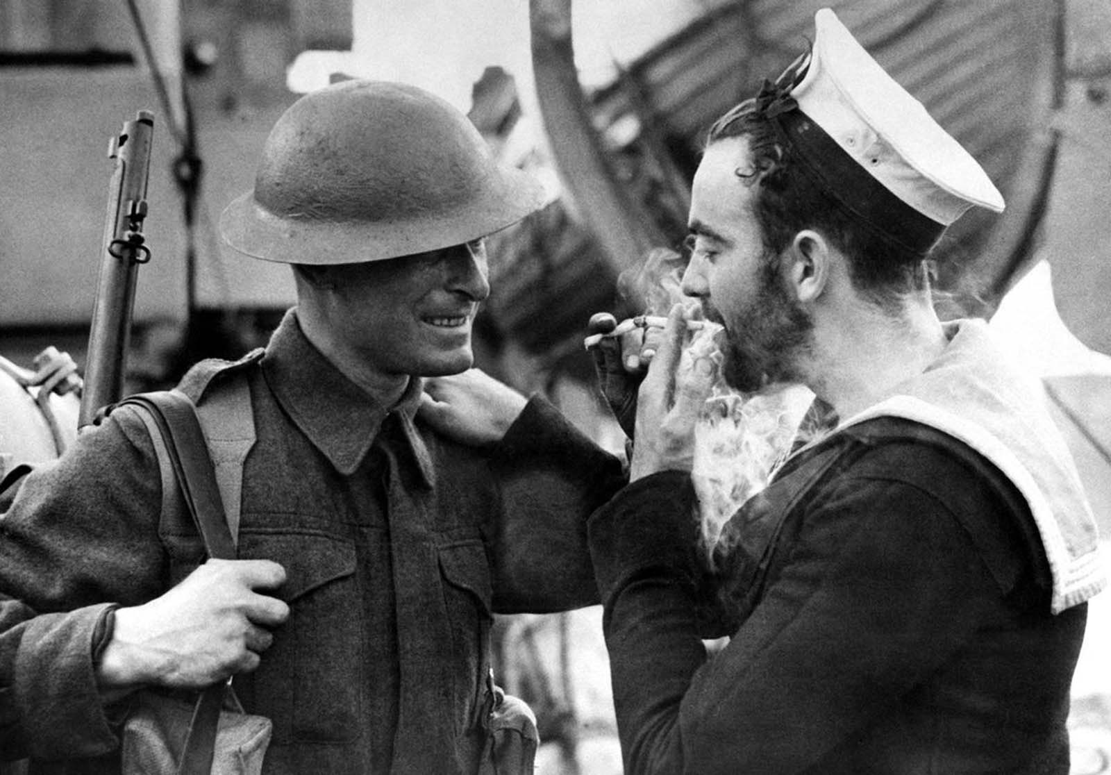 Two examples of Britain's war forces, a soldier in battle dress and a bearded Canadian sailor share a light at an English port, on January 14, 1941.