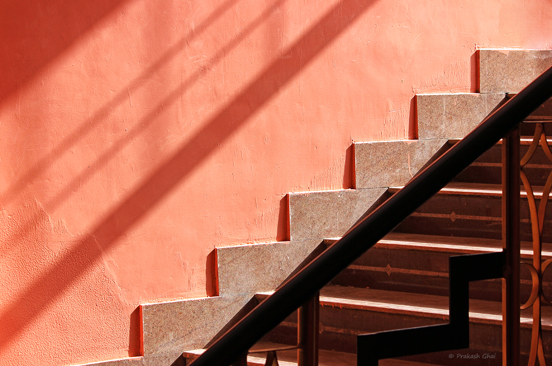 A Minimalist Photograph of Staircase with pink wall and shadows.