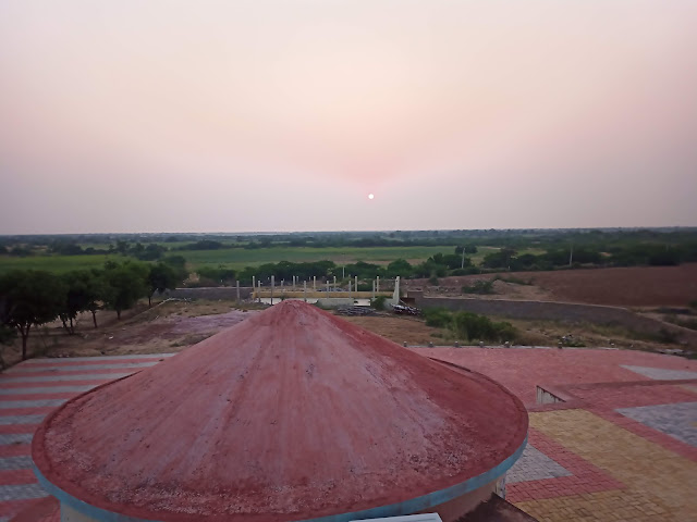 Sunset over Rann of Kutch, with huts in foreground and trees in background