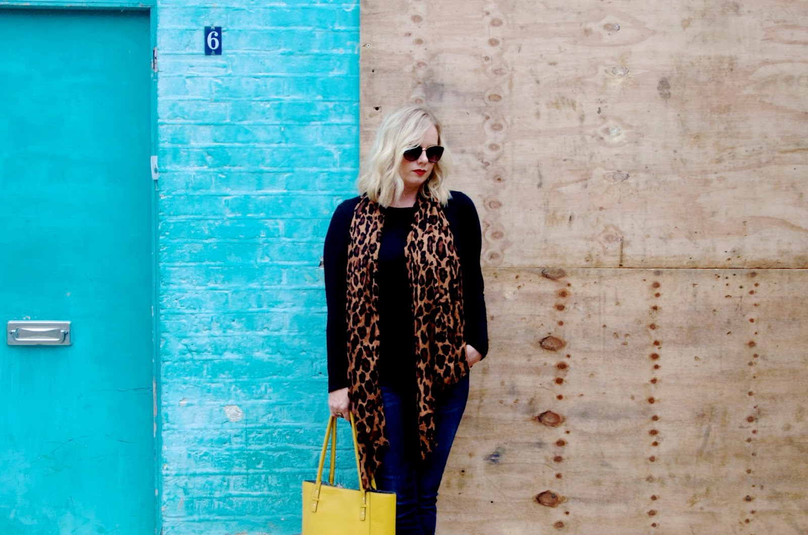 Leopard Print Scarf and long sleeve black t-shirt with jeans and a blue wall