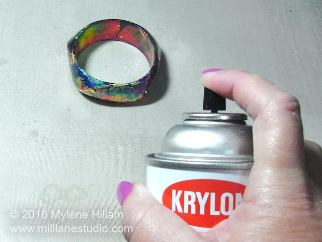 Spraying the alcohol ink painted bangle with clear acrylic spray.