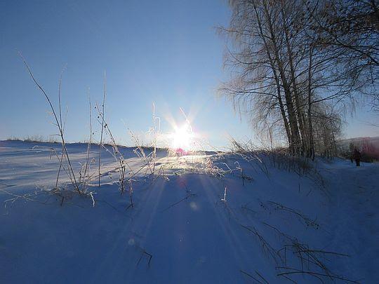 Słońce światłem muska obielone zagony i szkliste trawy.