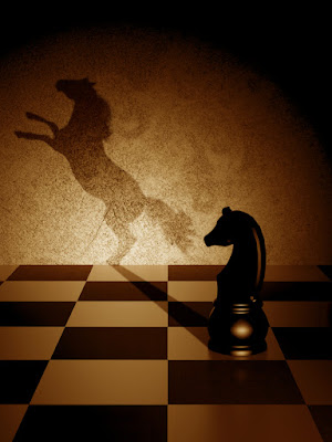 a pawn on a chess board casts the shadow of a stallion