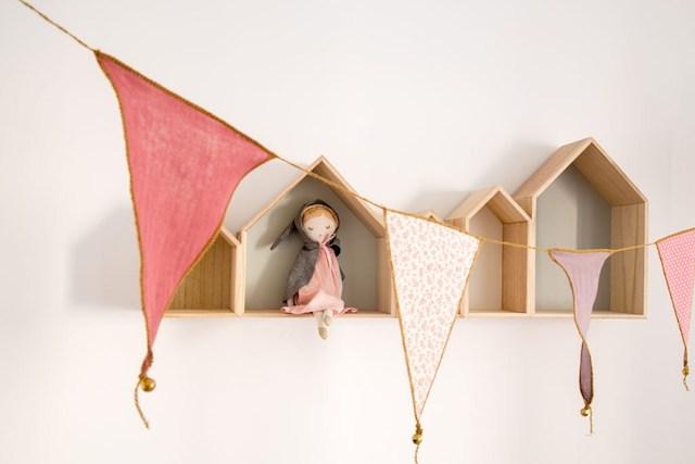 Banderines de tela y casitas de madera decorando un dormitorio infantil
