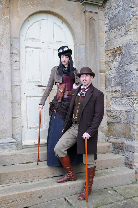 A man and women dressed in matching steampunk clothing with walking stick canes, goggles and hats.