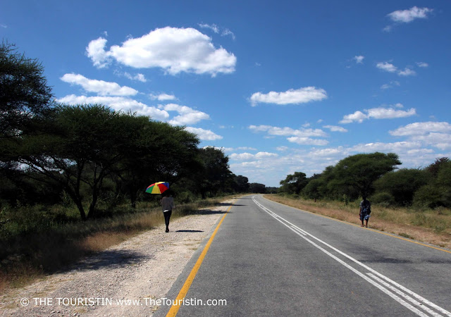 Pedestrians walking on the side of the road in the wildlife corridor of the Caprivi Game Park and the Kwando Core Area in Namibia