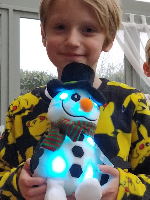 child with autism wearing pokemon pyjamas holding light up snowman sensory toy