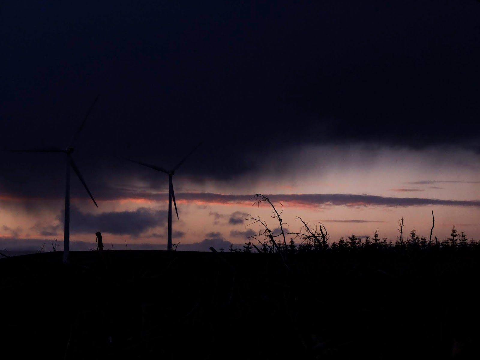 Very dark, navy rain clouds and two windmills to the left of the photograph.