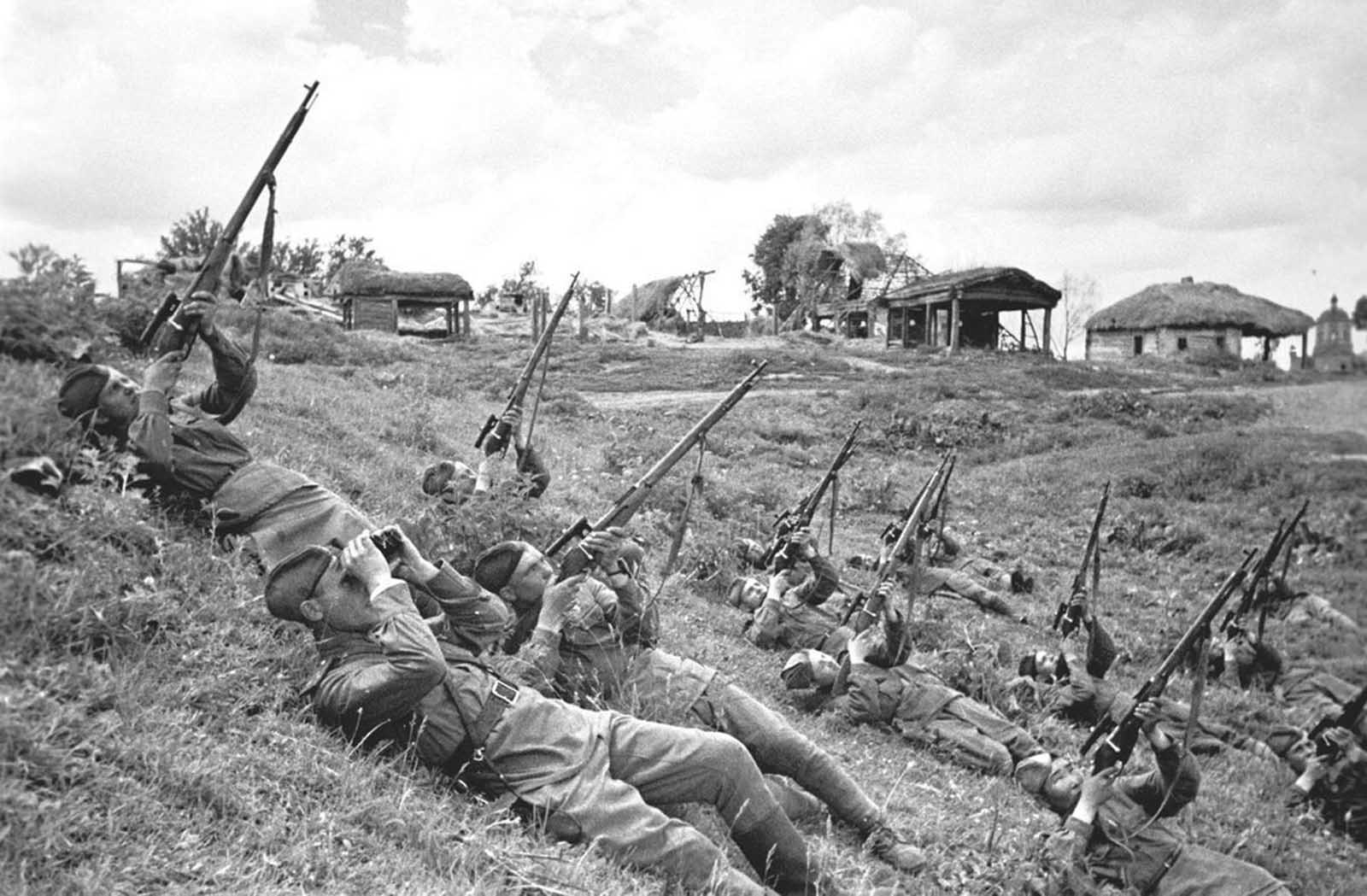 Soviet soldiers, on their backs, launch a volley of bullets at enemy aircraft in June of 1943.