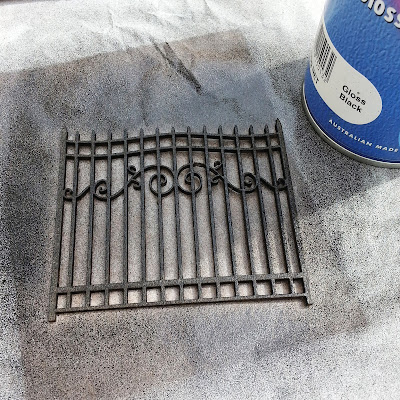 Spraypainted chipboard scrapbooking gate with a can of black spray paint next to it.