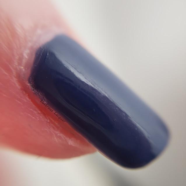 Dark dusty blue nail polish with a glossy creme finish