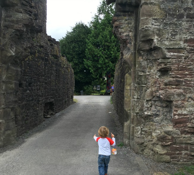 Abergavenny-castle-entrance-and-a-toddler-carrying-a-bag-full-of-stickers