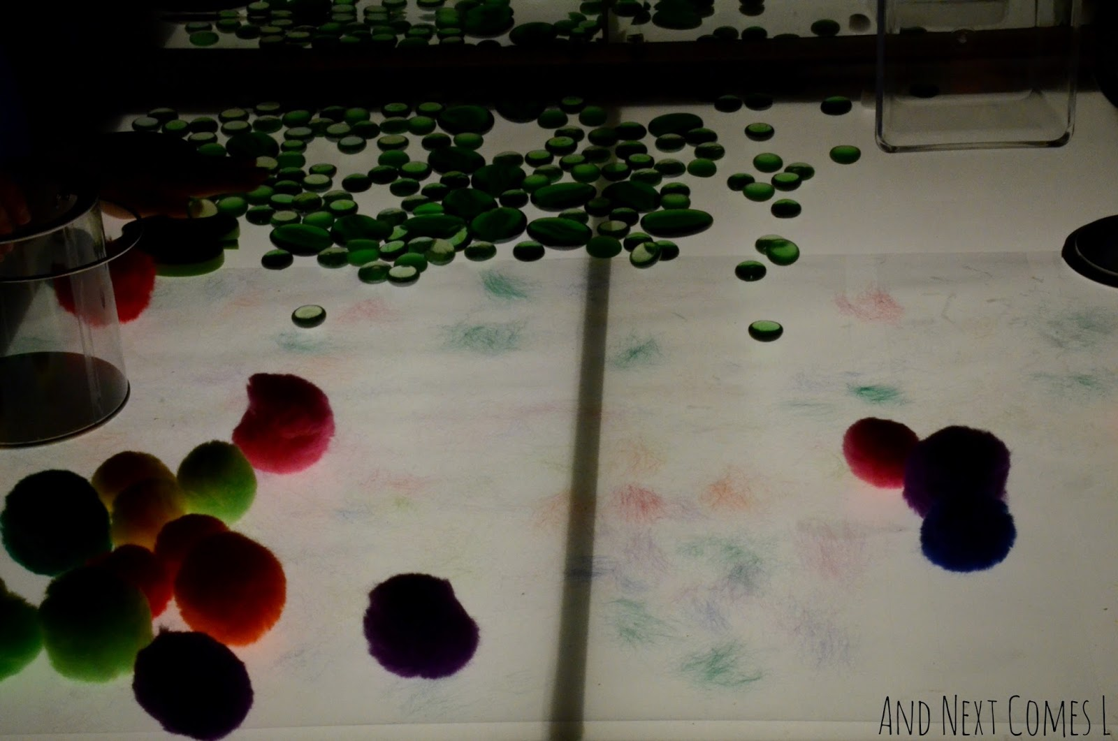 Open ended exploration after creating pom pom art on the light table from And Next Comes L