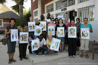 The Senegal medical team and translators holding Tostan health and human rights posters.