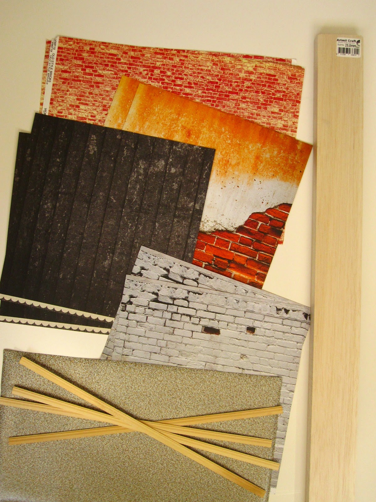 A selection of scrapbook paper sheets with distressed brick, plaster and wood patterns. A lenght of balsa wood and several lengths of dolls' house miniature skirting board.