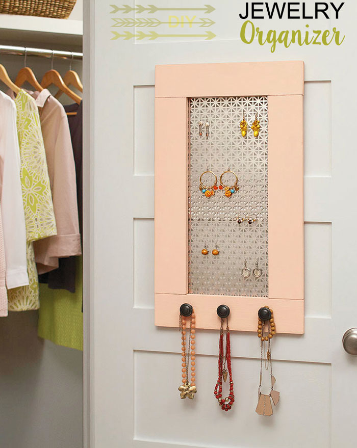 pink jewelry organizer made with wood and metal sheet, hanging on the closet door.