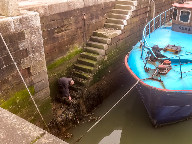 Photo of Phil retrieving the brush from the other end of the marina