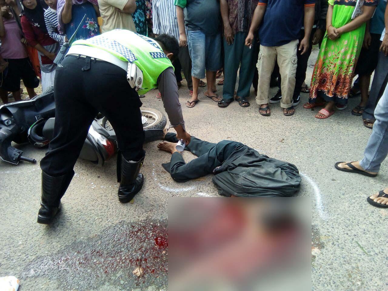 Personel Satlantas melakukan olah TKP di lokasi tabrakan yang menewaskan pengendara sepedamotor.