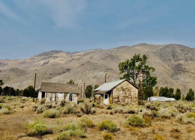 dilapidated shacks, sagebrush foreground, golden hills background