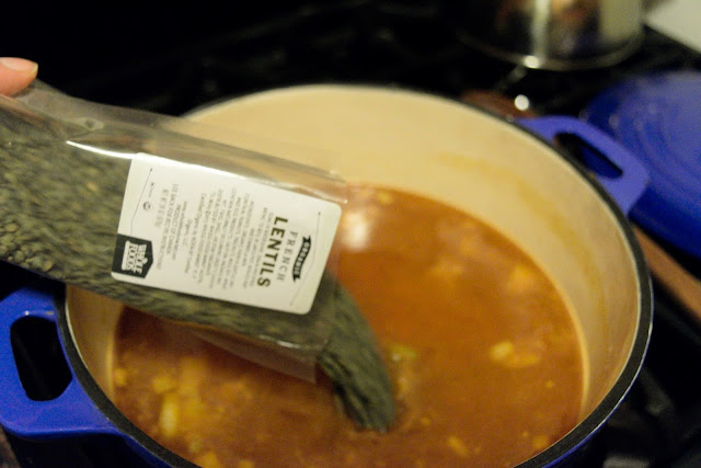 Dried lentils being added to the pot.